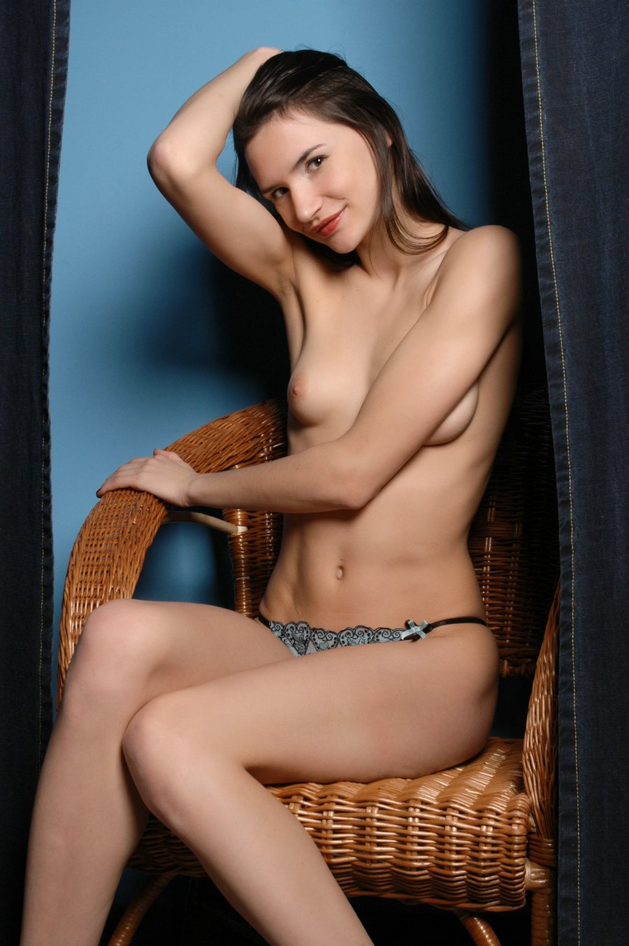 蓝色背景室拍藤椅上的长头发美模